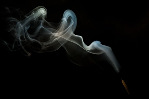 burning incense stick on black